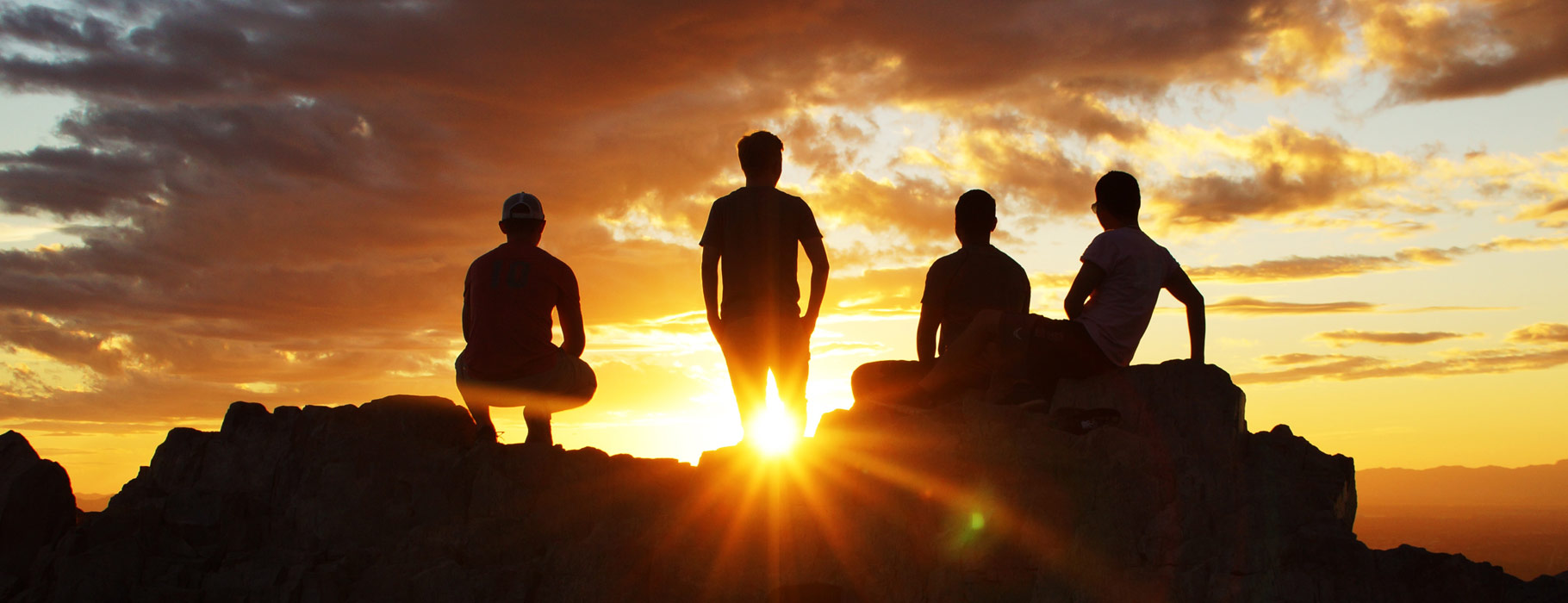 Four people watching the sunset from the top of a rock
